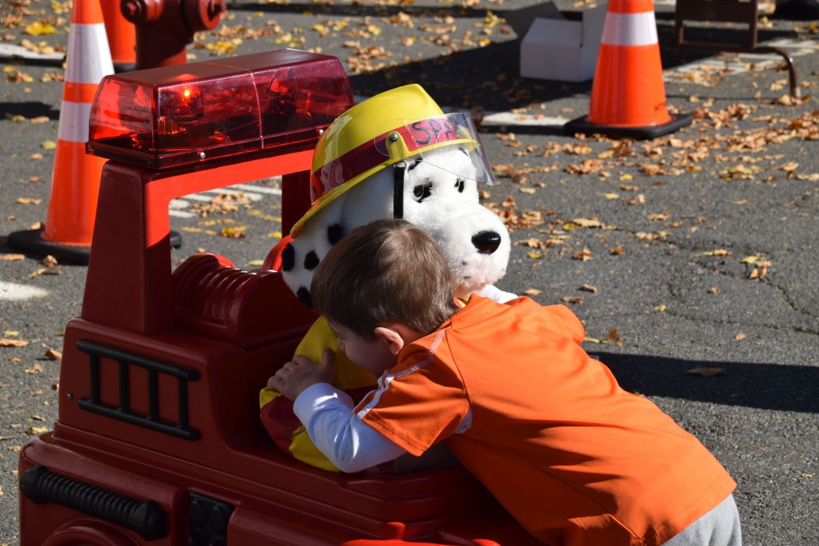 Child hugging Sparky the Fire Dog